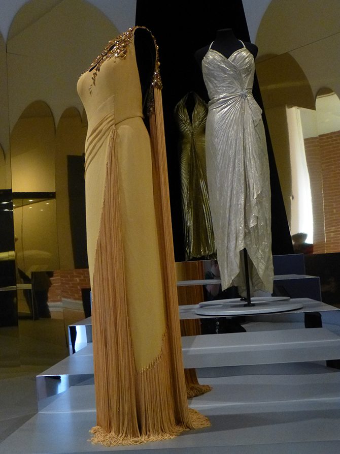 (foreground) Charles Le Maire (1897-1985), designer, Evening gown (1952), silk, bugle beads, fringing; originally made for The Snows of Kilimanjaro (Henry King, 1952); worn by Monroe in publicity photos, 1953. (middle) William (Jack) Travilla (1920-90), designer, Evening gown (1953), silver lamé; made for Gentlemen Prefer Blondes (Howard Hawks, 1953); worn by Monroe to the Los Angeles Herald Examiner Charity Event, 1953 and the Photoplay Magazine Awards,1954. (Collection of Greg Schreiner, Los Angeles). (rear) Gold lamé gown (replica) of one designed by Travilla, worn by Monroe in Gentlemen Prefer Blondes. (Americana Silver Screen Collection, Los Angeles). Installation photo: Inga Walton.