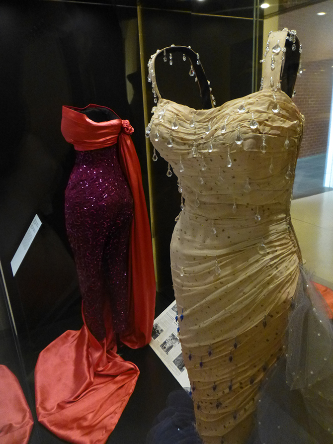 William (Jack) Travilla (1920-90), designer: (background) Sequinned pant suit and matching cloak (1955), silk, sequins, worn by Monroe in The Seven Year Itch (Billy Wilder, 1955) & (foreground) Evening gown (1954), silk, tulle, glass beads; Academy Award nominee for Best Costume Design (Colour, 1955), worn by Monroe in There's No Business Like Show Business (Walter Lang, 1954). (Colección Maite Minguez Ricart, Barcelona). Installation photo: Inga Walton.