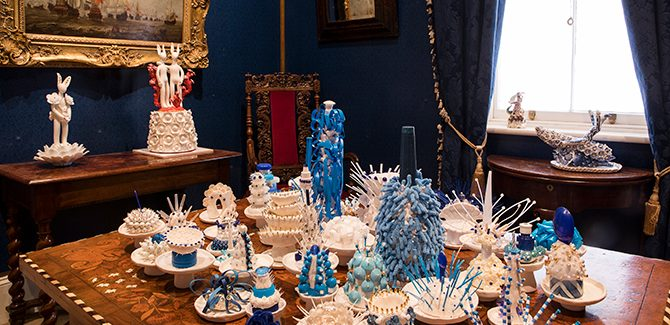 The Blue Room, installation by Vipoo Srivilasa, (on centre table) Collective Sea Life (2016), 43 items, porcelain & mixed media (dimensions variable). (on back table) (left) Hare: Deity of Abundance (2016), porcelain, glazed, Swarovski crystals, gold lustre, mixed media, 40 x 20 x 20 cm. (right) Deity of Creativity & Friendship (2016), multi-coloured layers of glazed ceramic, enamel paint, 58 x 24 x 24  cm. (windowsill table) Happy Ride III: Deity of Journey & Leadership (2016), cobalt pigment on porcelain, gold lustre, 18 x 20 x 36 cm. (on wall) Unknown (in the manner of Abraham Storck, 1635-1710), A Naval Battle Depicting Ships Carrying the Dutch and English Flags (c.1670), oil on panel, 61 x 86 cm, (Foundation Collection, The Johnston Collection). Photo: Adam Luttick.
